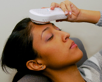 image of woman holding ambi to forehead to relieve migraine pain